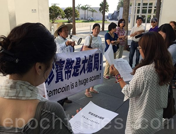 一群華裔投資人在聖貝納迪諾縣安大略會議中心 (Ontario Convention Center) 外抗議「美國富豪集團」,稱其發行的珍寶幣為一個大騙局,並向與會者散發資料。(大紀元)