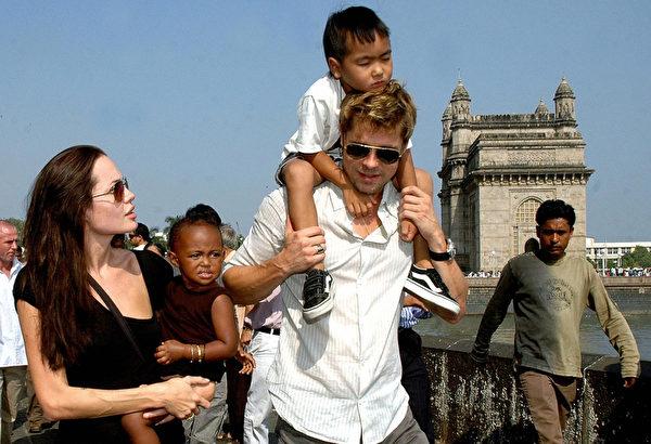 2006年朱莉、皮特与两个养子在印度孟买,皮特肩上为5岁的麦多克斯。(STR/AFP/Getty Images)