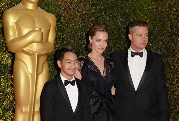 2013年11月,朱莉(中)获颁美国影艺学院颁发的人道大奖,布拉德‧皮特带养子麦多克斯出席颁奖礼。(ROBYN BECK/AFP/Getty Images)