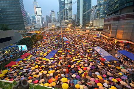 2014年10月28日傍晚開始,逾萬香港人在金鐘雨傘廣場舉行要求真普選的「雨傘運動滿月紀念活動」。期間,大家撐傘87秒回應警方在9月28日針對市民釋放了87個催淚彈。(潘在殊/大紀元)