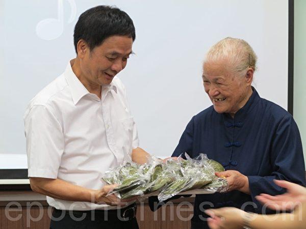 陈绸阿嬷(右)带着志工们手作的草仔粿,送给与会来宾及受保护管束学员,由高雄地检署检察长周章钦(左)代表接受。(李晴玳/大纪元)