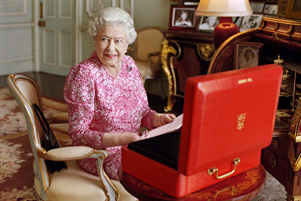 女王近日在白金汉宫私人接见室中,查看政府官方档,旁边放置着其官方红箱子。她几乎每天都会收到这个红箱子,装着政府官员、国协等的重要信件。(Mary McCartney/Her Majesty Queen Elizabeth II via Getty Images)