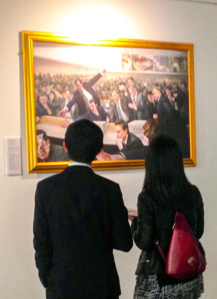二零一五年九月二日,「真善忍」美展的每幅作品在東倫敦傲案中心(The Proud Archivist)展出,兩位華人青年認真觀看畫作。(明慧網)