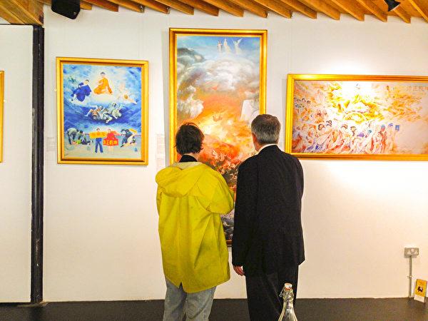 觀眾正在認真觀看「真善忍」美展的畫作。(明慧網)