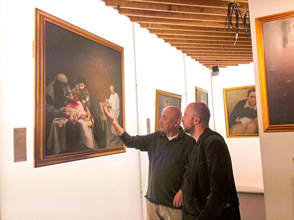 製片人維森特(Vicent)(右)和世界維吾爾族大會英國代表安華.托蒂(左)一起在觀看畫作《活摘器官的罪惡》。(明慧網)