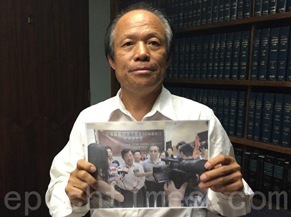 珍寶幣抗議者劉因全手舉亞凱迪亞市議員鄂志超(John Wuo)為珍寶幣站台的照片。(劉菲/大紀元)