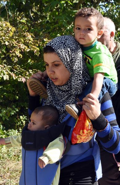 2015年9月21日,克羅地亞和匈牙利邊界Botovo火車站,一位難民母親背著她的兩個幼兒。匈牙利成為今年歐洲難民危機最緊繃的地區,超過22萬人從希臘通過西巴爾幹進入塞爾維亞以及克羅地亞、匈牙利等地。(STRINGER/AFP)