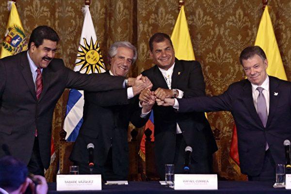 2015年9月21日,在基多舉行的會議,經過一個多月邊界爭議和召回大使等衝突後,哥倫比亞總統馬杜羅(左一)和委內瑞拉總統馬杜羅(右一)終於握手言和,並恢復外交,逐步開放邊界。中間兩位為調解人烏拉圭總統巴斯克斯和厄瓜多爾總統科雷亞。(JUAN CEVALLOS/AFP/Getty Images)