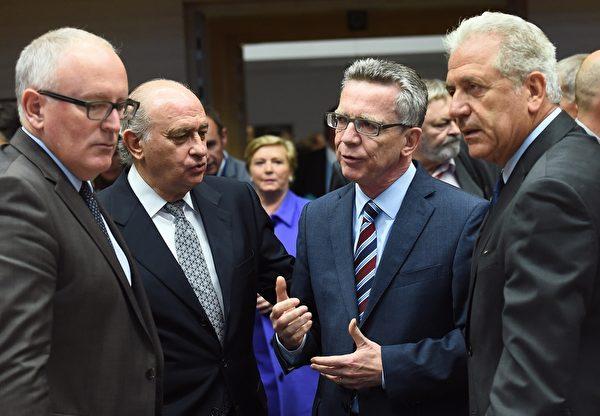 2015年9月22日,布魯塞爾,德國內政部長德梅齊埃(右2),西班牙內政大臣迪亞斯(左2),歐盟委員會負責移民,民政和公民事務的阿夫拉莫普洛斯(右1)和歐盟委員會副總裁蒂默曼斯參加歐盟內政部長會議,討論難民問題。此次會議以「多數票」通過分配12萬抵歐難民方案,但數個中歐國家表達憤怒,計劃將本案提交到歐洲法院。(EMMANUEL DUNAND/AFP/Getty Images)