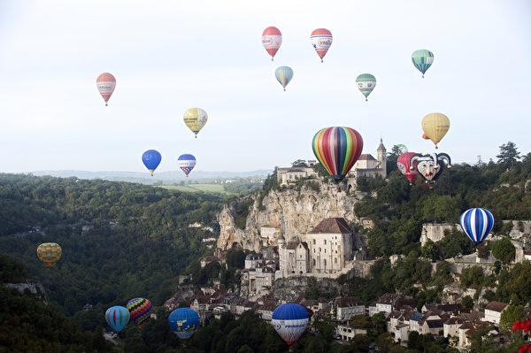 2015年9月26日,法國勞卡馬杜爾熱氣球節期間,五顏六色的熱氣球飛越懸崖頂部的中世紀小鎮羅卡馬杜爾。(REMY GABALDA/AFP)