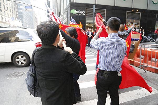 2015年9月26日,纽约华尔道夫酒店附近,扛着中共血旗欢迎习近平的队伍与维权访民起冲突。(施萍/大纪元)