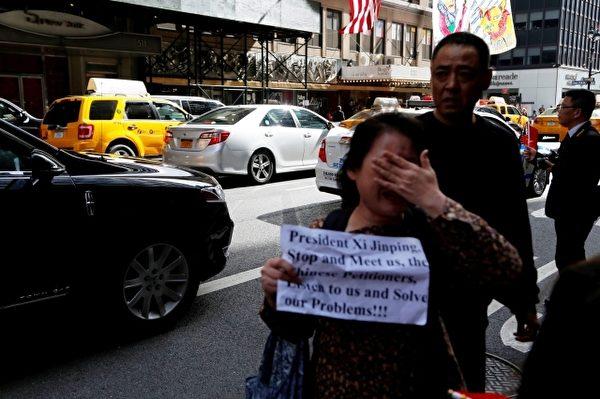 访民在华尔道夫酒店旁边抗议现场哭泣(施萍/大纪元)
