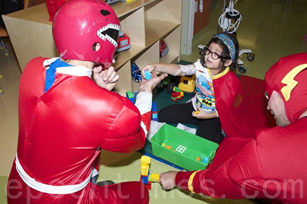 图:Isabel Vasquez和超人开心的玩游戏。(杨帆/大纪元)