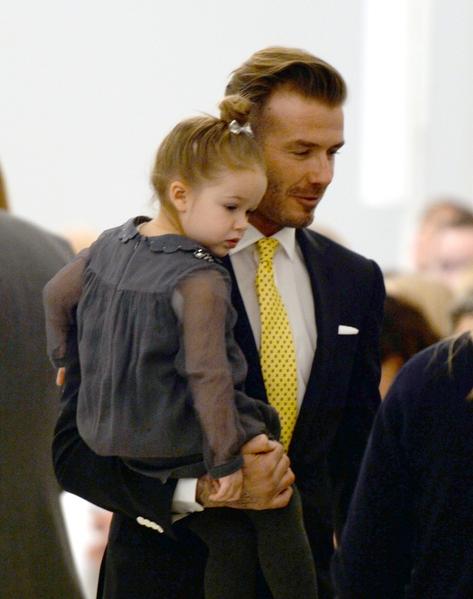 2014年2月9日,大卫‧贝克汉姆抱着哈珀(小七)参加纽约2014秋冬时装周维多莉亚品牌时装的专场秀。(DON EMMERT/AFP/Getty Images)