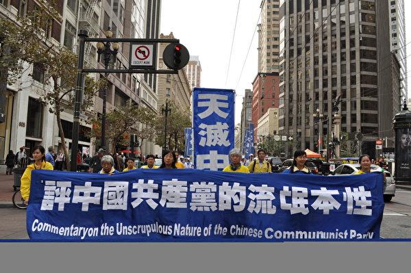 《九评共产党》于2004年11月在大纪元刊发社论后,引发全球三退(退党、退团、退队)大潮,图为2014年10月15日,来自世界各地的部分法轮功学员在旧金山市中心游行时向路人展示九评共产党的主要内容。(唐风/大纪元)