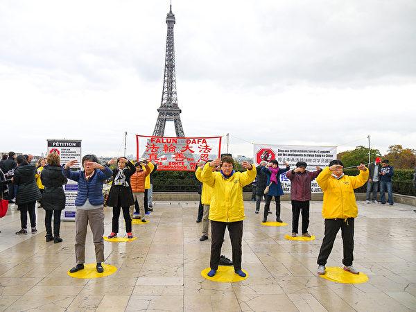 法轮功学员在巴黎艾菲尔铁塔下的人权广场上演示功法。(明慧网)