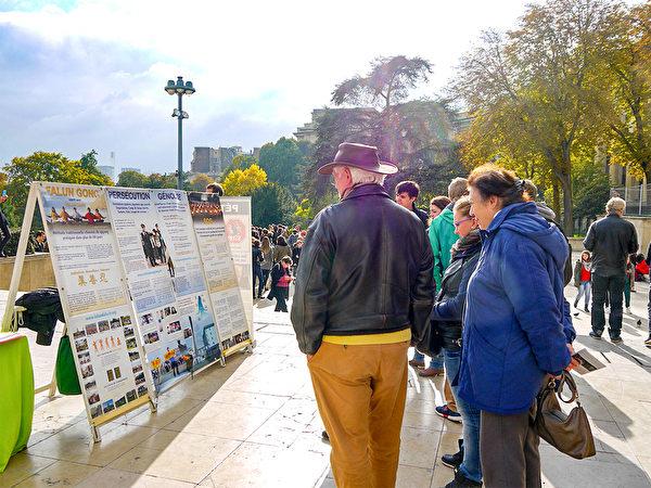 巴黎艾菲尔铁塔下,游客认真阅读法轮功真相展板。(明慧网)