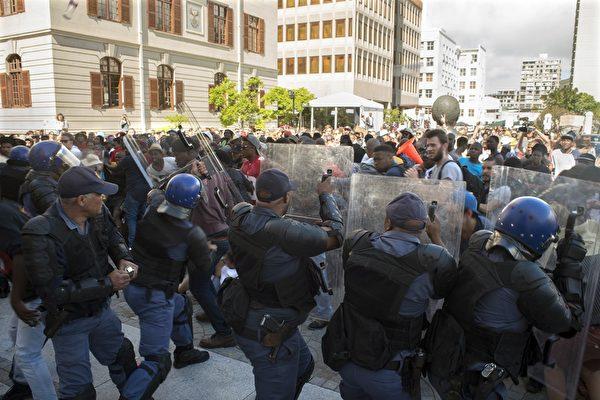 2015年10月21日,南非学生在开普敦的国会外抗议全国大学学费调涨,镇暴警察与示威学生起冲突。(RODGER BOSCH/AFP/Getty Image)