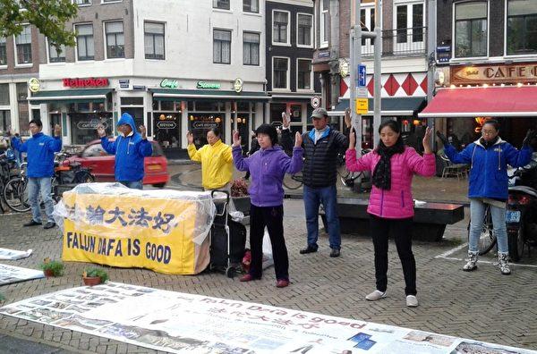 荷蘭部分法輪功學員在阿姆斯特丹唐人街舉辦講真相活動,演示法輪功功法。(明慧網)