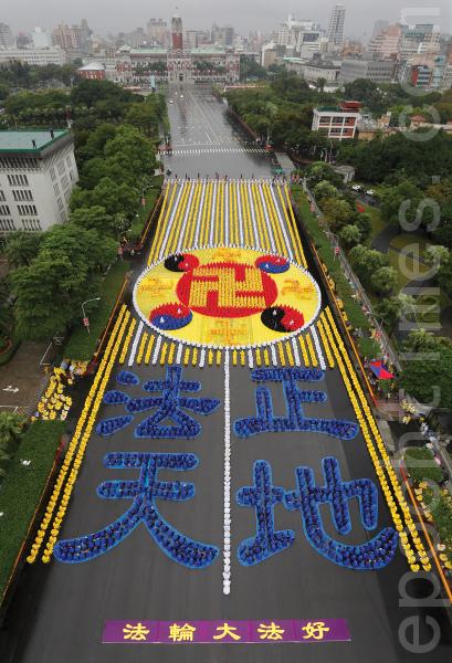 """六千名台湾法轮功学员不畏寒天细雨,17日在总统府前的广场,排出""""法正天地""""及法轮功的标志法轮图形,场面壮观。(李丹尼/大纪元)"""