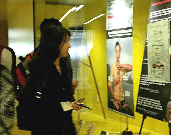 圖:11月5日,加州大學聖地亞哥分校(UCSD)法輪大法俱樂部在校園內擺信息臺,演示功法並介紹法輪功真相。圖為學生正在閱讀展覽櫥窗內揭露中共活摘法輪功學員器官的海報。(大紀元)