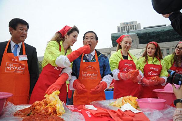 """第二届""""首尔泡菜庆典""""期间,首尔市长朴元淳(左3)与嫁到韩国的外国籍媳妇共同腌制越冬泡菜,并送给首尔的孤老弱势族群。(首尔市政府提供)"""