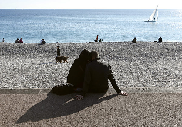 法國一對情侶在海蔚藍海岸尼斯海灘享受冬陽。(VALERY HACHE/AFP)