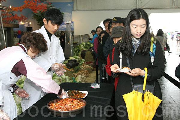 第二届首尔泡菜庆典期间,游客免费品尝泡菜。(全宇/大纪元)