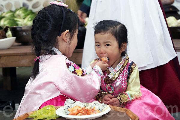 第二届首尔泡菜庆典期间,孩子品尝泡菜饭。(全宇/大纪元)