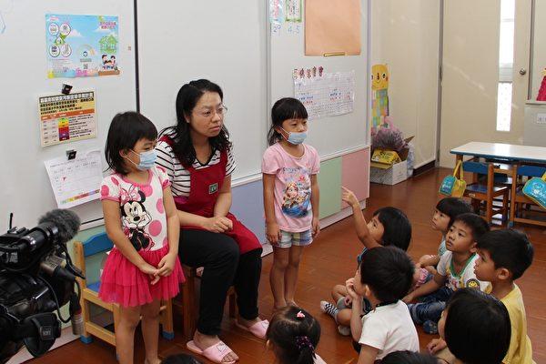 北园国小幼儿园上课时,老师指导小朋友戴口罩的正确方式,并进行空品旗颜色的宣导。(李撷璎/大纪元)
