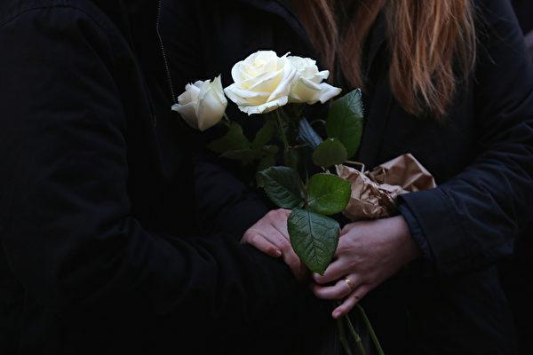 2015年11月15日,巴黎,一個女子拿著三朵白玫瑰在夏洪街(Rue de Charonne)上的餐廳前哀悼恐怖攻擊中的死難者。(Christopher Furlong/Getty Images)