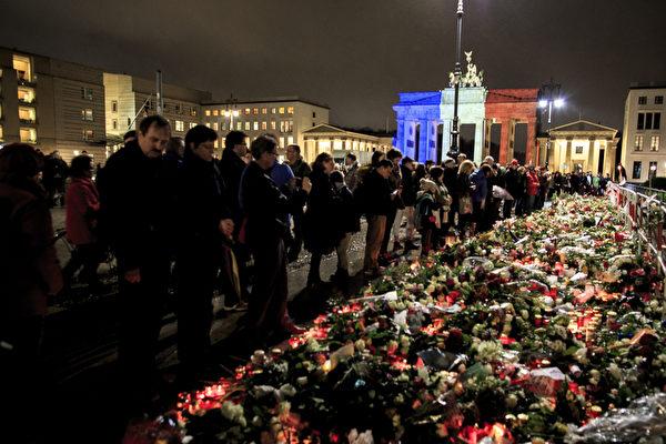 2015年11月15日,德國柏林,勃蘭登堡門照著法國國旗的顏色。人們在法國大使館門口附近擺滿蠟燭和鮮花,悼念巴黎恐怖攻擊受害者。 (Carsten Koall/Getty Images)