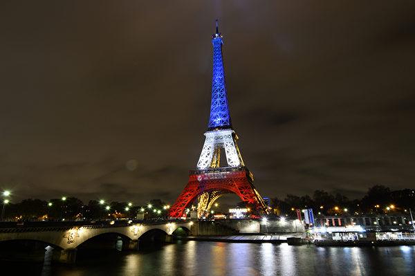 2015年11月16日,周一晚间,巴黎恐袭后的艾菲尔铁塔,与协和广场的摩天轮,同时亮起红白蓝三种颜色,象征着法国上下团结一致的决心。13日的巴黎发生的恐怖袭击造成129人死亡,350多人受伤,(BERTRAND GUAY/AFP)