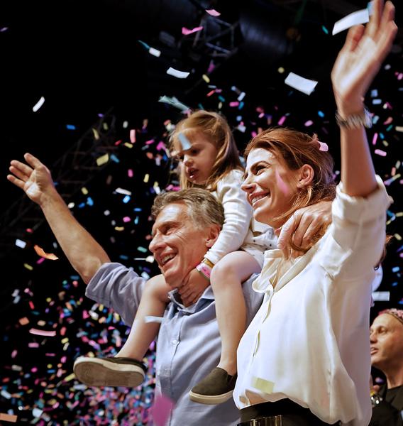 2015年11月22日,阿根廷的总统大选由亲市场派领袖马克里胜出,预示了左翼政府12年执政的结束。马克里预计将成为这个拉丁美洲第3大经济体1990年代以来经济理念最自由派的总统。图为马克里(左)在布宜诺斯艾利斯的总部和他的妻女一同和民众挥手接受庆贺。(AFP)