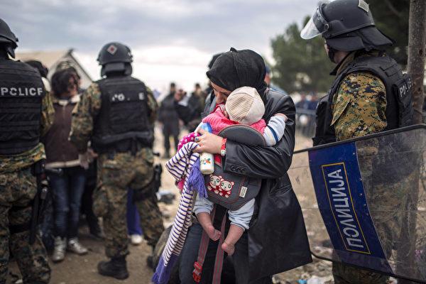 2015年11月22日,在希腊与马其顿边边境杰夫格里雅,一个难民妇女和她的孩子走过马其顿警方附近。11月19日联合国难民署说,位于难民主要通往北欧的路径上的塞尔维亚和马其顿目前已经开始限制难民入境,只允许来自某些战乱国家的难民。(ROBERT ATANASOVSKI/AFP)
