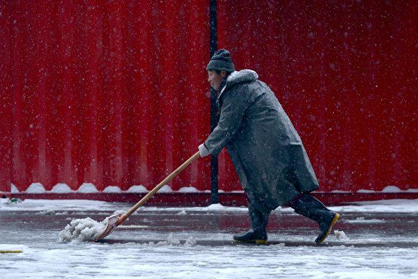 2015年11月22日,北京遭遇近5年罕见暴雪袭击,降雪量最高达15毫米,暴雪下的北京有近700班航班延误或取消。图为一位民众正在清理积雪。(WANG ZHAO/AFP)