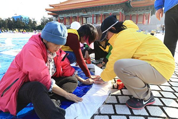 台湾法轮功学员齐心协力,进行排字前的准备工作。(白川/大纪元)