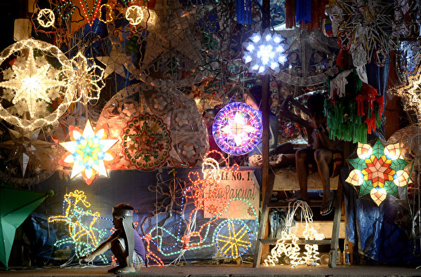 """2015年12月22日,马尼拉街头展示了当地称为""""parol""""的圣诞彩灯,图案类似于伯利恒之星星形圣诞灯笼,以竹子为支架,铺上纸张制成。根据菲律宾的传统和信仰,此彩灯也代表了光战胜黑暗。(NOEL CELIS/AFP)"""
