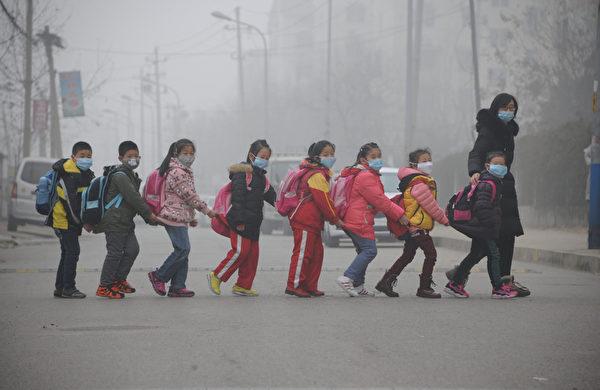 2015年12月24日,山东省济南,成群学生戴着口罩由大人带领走在过街的路上。因雾霾范围持续扩大,中国东部严重的空气污染使得京津冀及周边地区当天发布红色预警的城市有10个。(AFP)