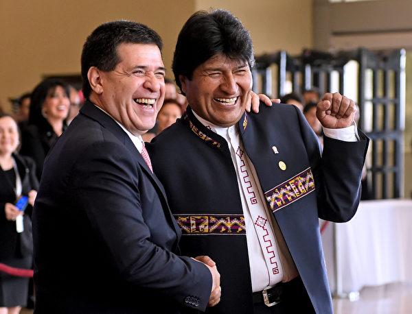 2015年12月21日,巴拉圭首都亚松森,南方共同市场首脑会议,巴拉圭总统奥拉西奥·卡尔特招呼玻利维亚总统莫拉莱斯(右)的到来。南方共同市场是巴西、阿根廷、乌拉圭、委内瑞拉和巴拉圭等南美洲国家的区域贸易协定。(MIGUEL ROJO/AFP)