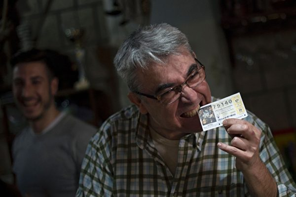 2015年12月22日,西班牙传统圣诞彩票于当地时间周二开彩,总彩金22亿欧元。共有1600张彩票中头奖,而且全部在南部城镇滨海罗克塔斯售出,头奖彩金6亿4千万欧元,即每张彩票可获40万欧元。图为当地一家酒吧的老板安东尼奥不可置信的咬着中奖号码79140的头奖彩票。(JORGE GUERRERO/AFP/Getty Images)