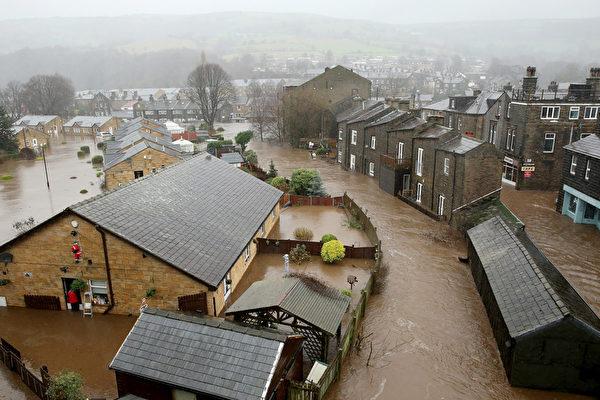 2015年12月26日,英国MYTHOLMROYD卡尔德谷镇,因降雨造成卡尔德河泛滥淹没街道。英格兰北部的水灾灾情使部分城镇宛如迷你威尼斯,包括名列旅游景点的历史性城镇约克,迫使数以百计民众撤离家园。(Christopher Furlong/Getty Images)