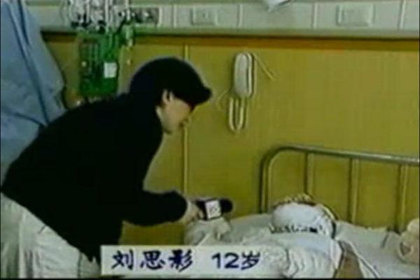 中央電視台「天安門自焚案」中的「燒傷病人」全身包裹,記者不穿衛生服,不戴口罩,大膽採訪。(視頻截圖)