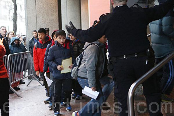 參加亨特學院高中入學考試的孩子在校警的指揮下,進入考場。(杜國輝/大紀元)