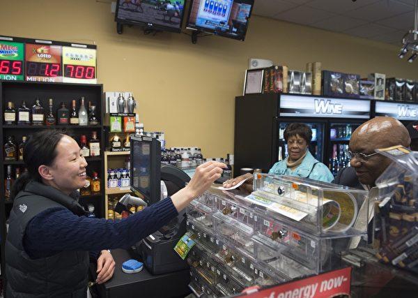 1月7日,在华盛顿特区的一家便利店,店主正在帮彩民购买劲球彩票。(Saul Loeb/Getty Images)