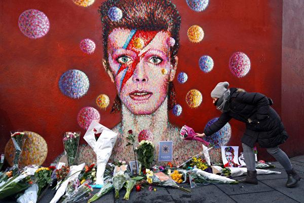 2016年1月11日,英国伦敦,一名女性歌迷于伦敦布里克斯顿的壁画前向大卫鲍伊(David Bowie)致意。英国知名摇滚乐手、演员及唱片制作人大卫鲍伊历经18个月的辛苦抗癌过程,仍不敌病魔于10日逝世,享寿69岁。(Carl Court/Getty Images)