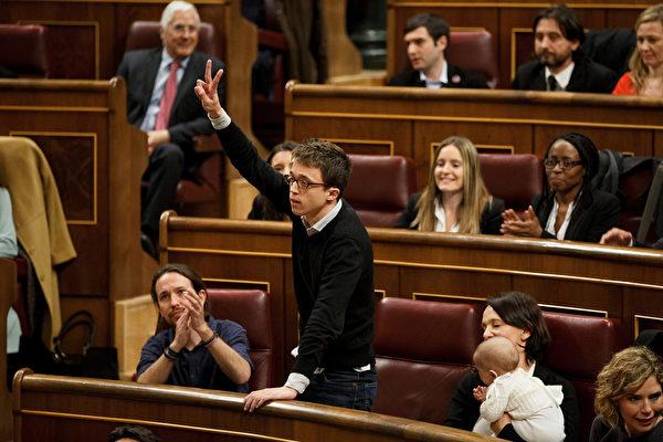 2016年1月13日,西班牙马德里,西班牙新一届议会召开会议,结果由57岁的工人社会党成员帕特克西·洛佩斯以130票的相对多数票当选议长。图为西班牙左翼新兴政党Podemos(我们可以党)发言人艾雷宏(Inigo Errejon)在会议进行中做了一个胜利的手势。(Pablo Blazquez Dominguez/Getty Images)