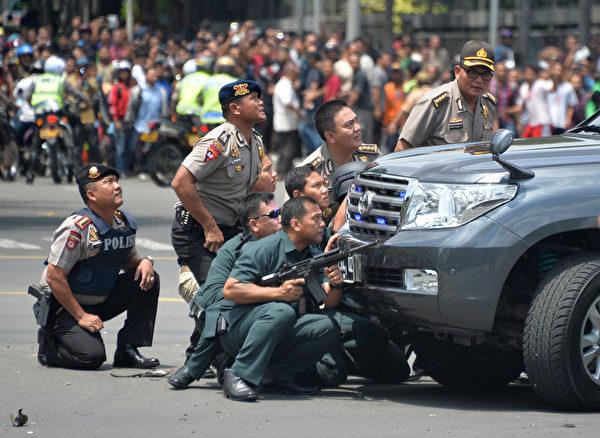 2016年1月14日,印尼首都雅加达市中心几处地方发生了爆炸和枪战,7人丧生,含5名攻击者与2名平民(包括1名警察)。图为印尼警方对歹徒展开反击,在车辆后面掩蔽。5名攻击者中,2人引爆自身的炸弹死亡外,另3人被击毙。(Bay ISMOYO/AFP)