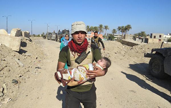 2016年1月14日,伊拉克安全部队战胜伊斯兰国夺回拉马迪两周后,因IS在城市近郊路边埋了很多炸弹和地雷,安全部队清理近郊Sufia区并撤离平民。图为撤离该区的平民和儿童。(MOADH AL-DULAIMI/AFP)