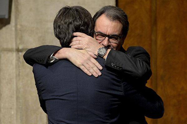 2016年1月14号,巴塞罗那政府宫,新内阁成员宣誓就职仪式上,即将离任的加泰罗尼亚自治区议会阿图尔·马斯(右)拥抱他的继任者普伊格德蒙特(左)。西班牙首相拉霍伊就在投票前表明,不会容许加泰罗尼亚独立,不过加泰罗尼亚自治政府表示,无论宪法法院如何裁决,不会改变他们推动独立决议的决心。(JOSEP LAGO/AFP)